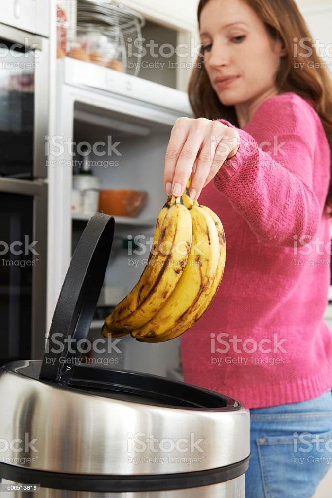 Woman Throwing Away Out Of Date Food In Refrigerator stock photo