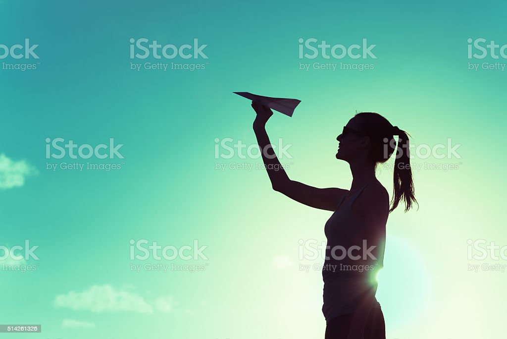 Woman throwing paper airplane stock photo
