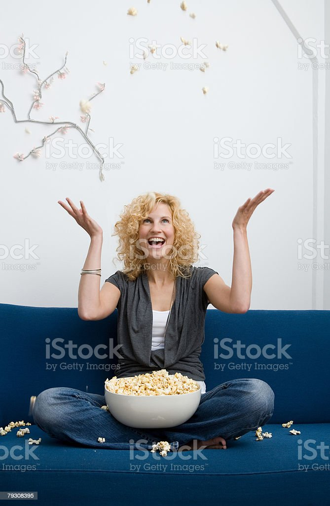 Woman throwing popcorn stock photo