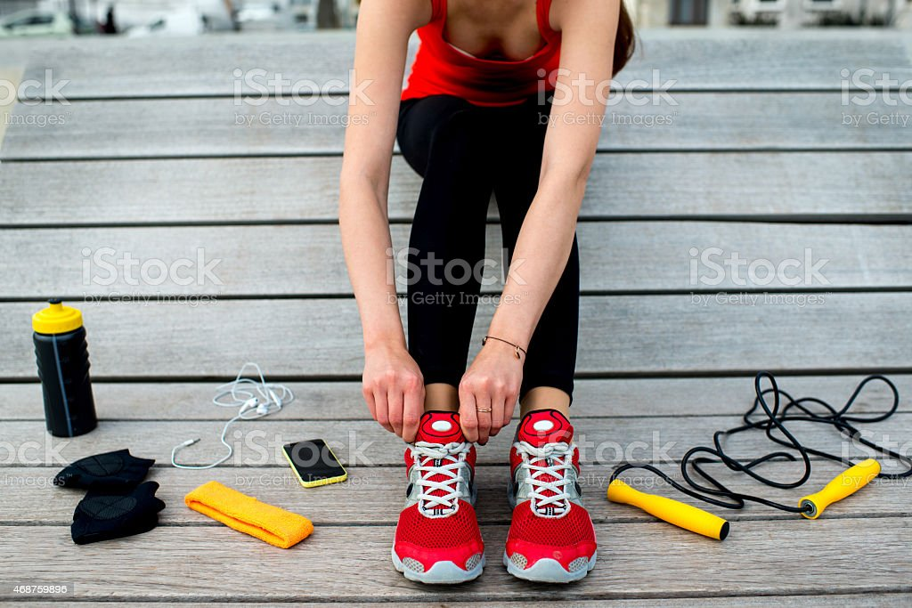 A woman tightens her sneakers for athletic activity stock photo
