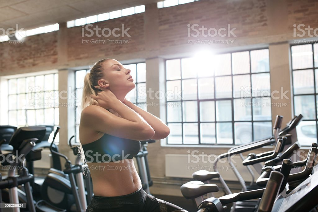 Woman tired after intense workout on gym bike stock photo