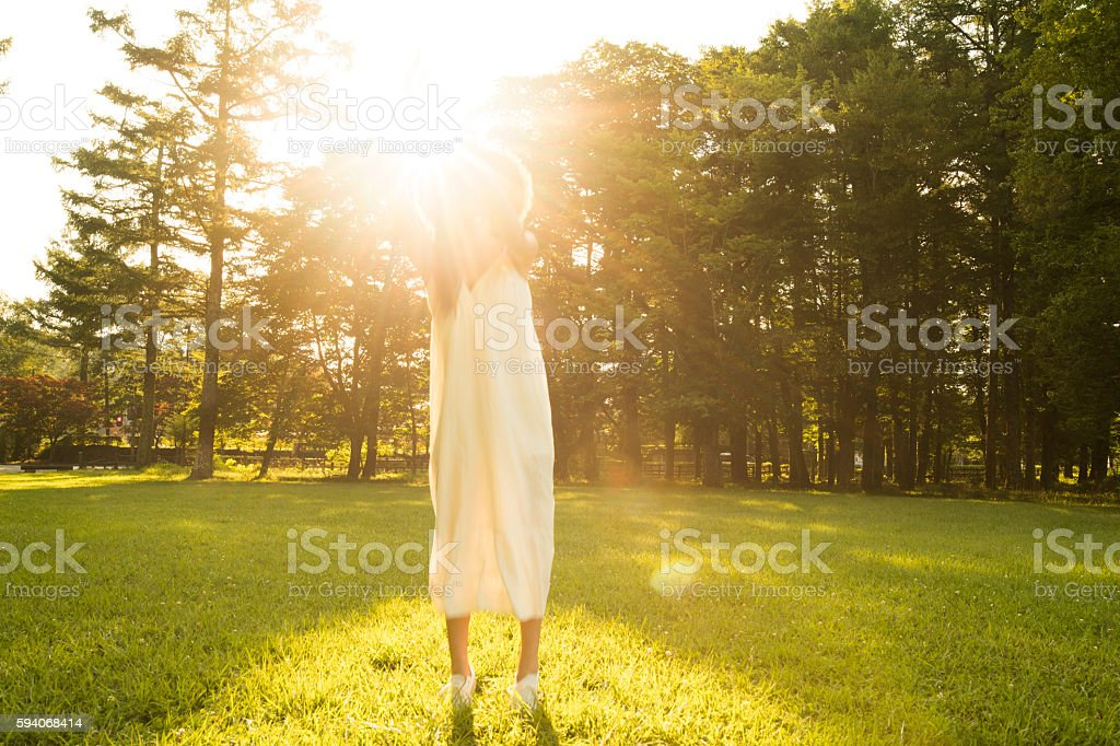 Woman to be illuminated by the sunset. stock photo
