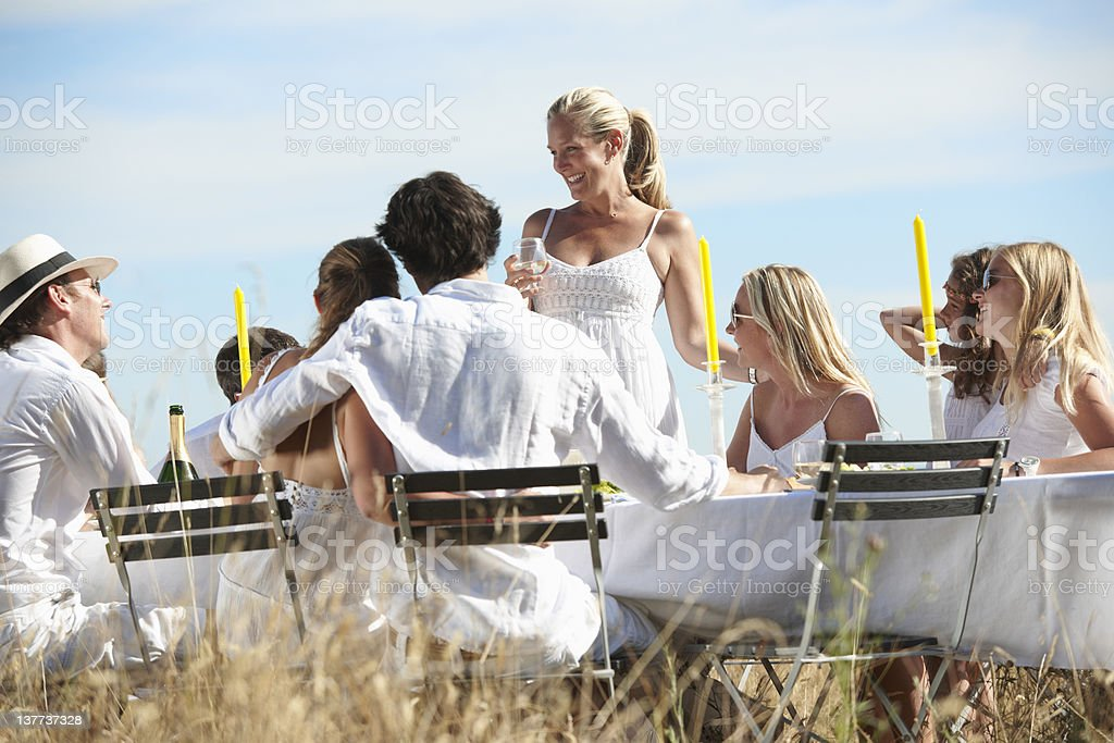 Woman toasting at table outdoors royalty-free stock photo