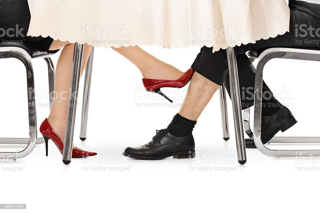 Woman touching a guy under a table stock photo