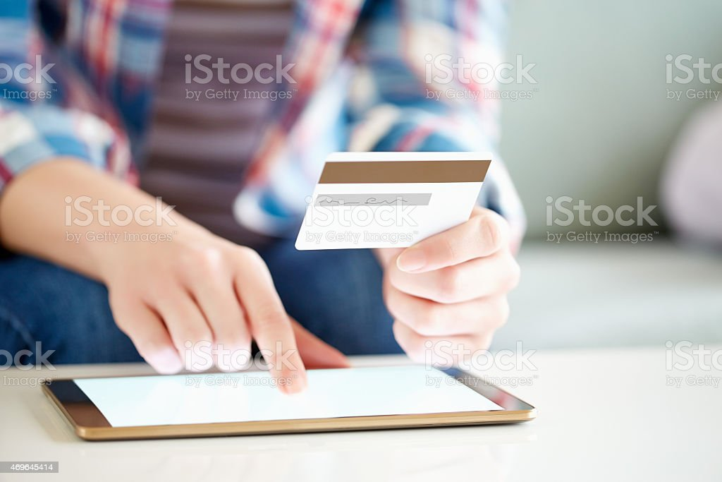 Woman touching digital tablet while holding credit card stock photo