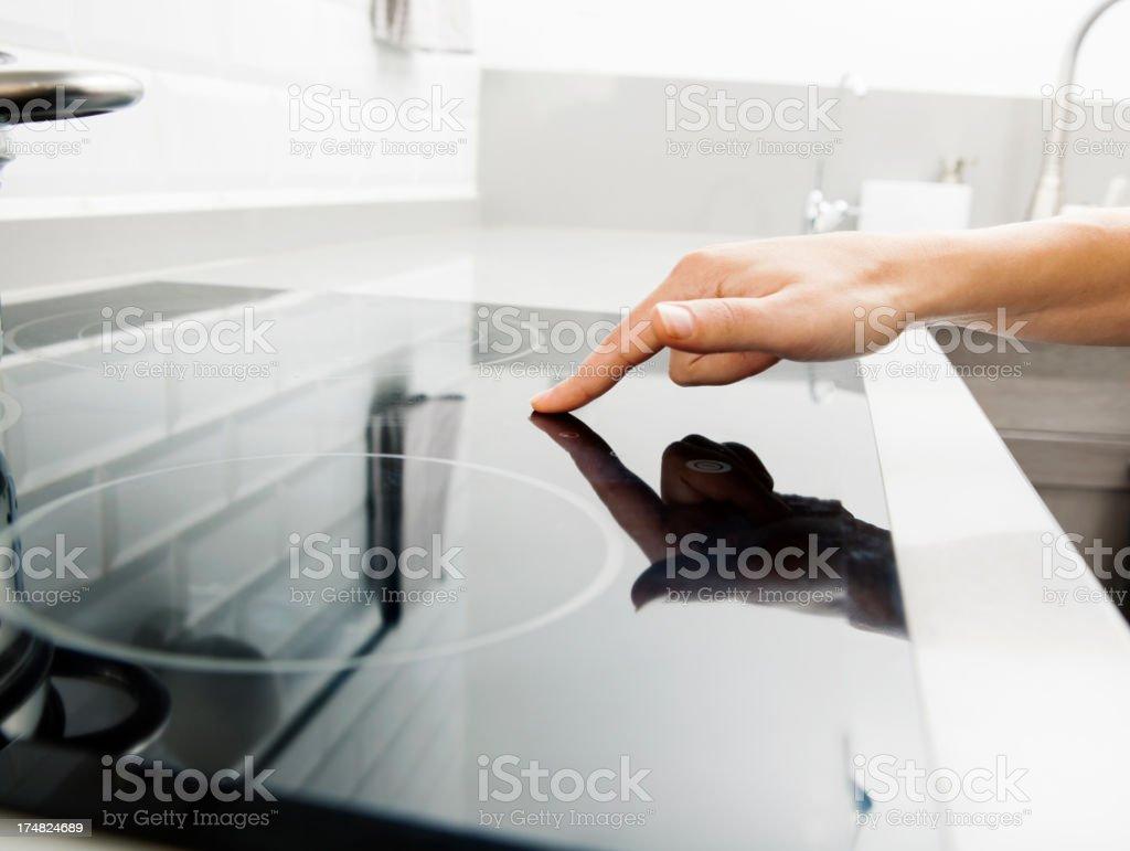 woman touching electric hob stock photo