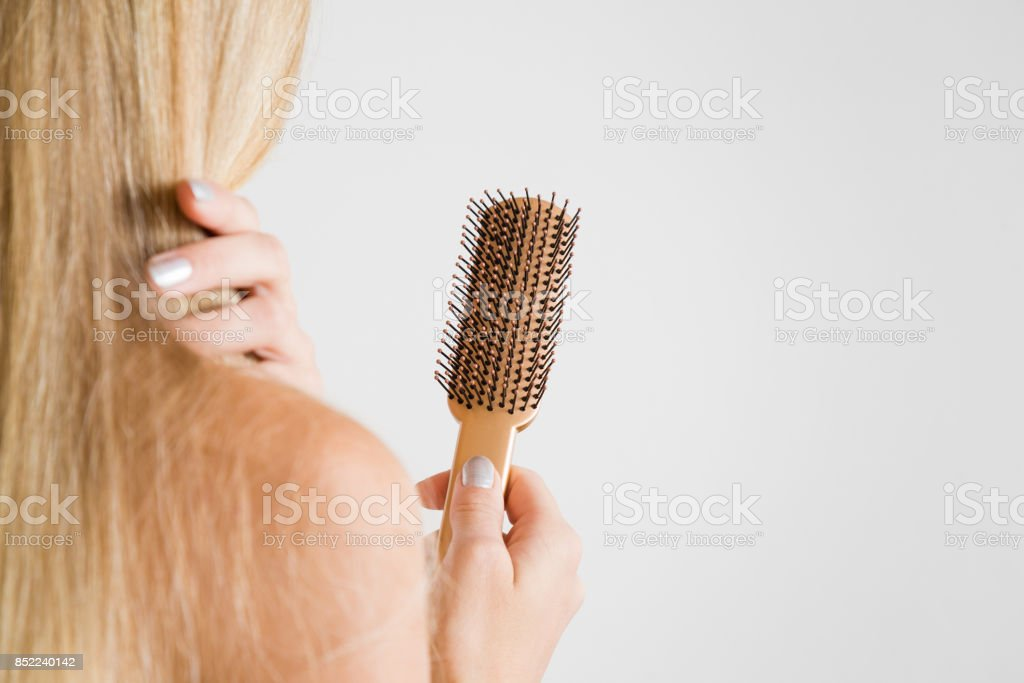 Woman touching hair and looking at the comb. Cares about a healthy and clean hair. Beauty salon. Empty place for a text on the gray background. stock photo