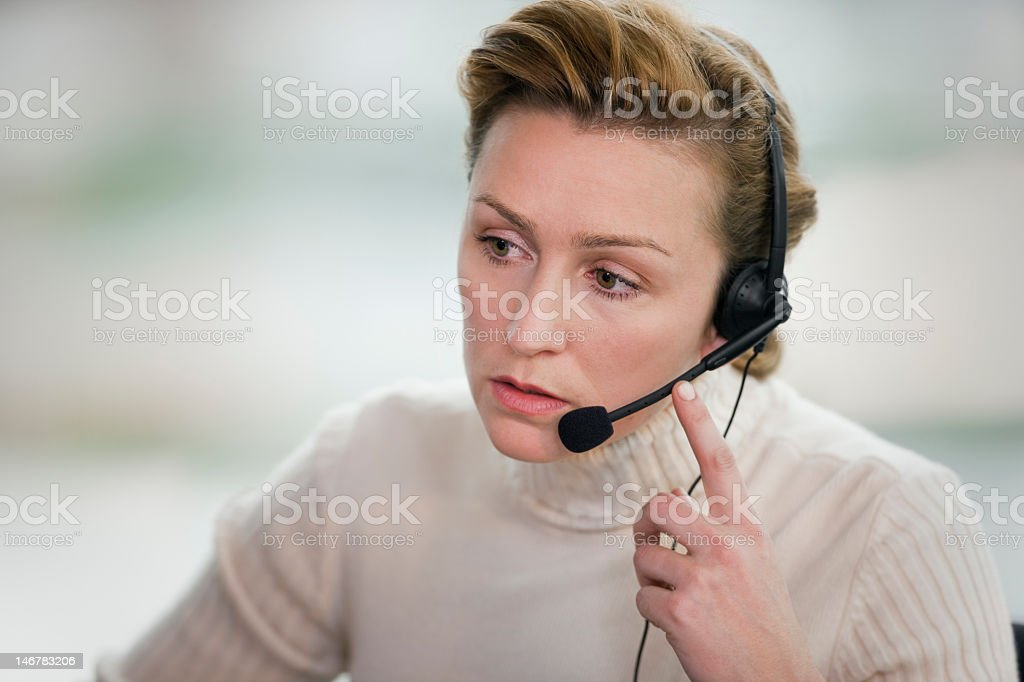 Woman touching headset and staring in front of her stock photo