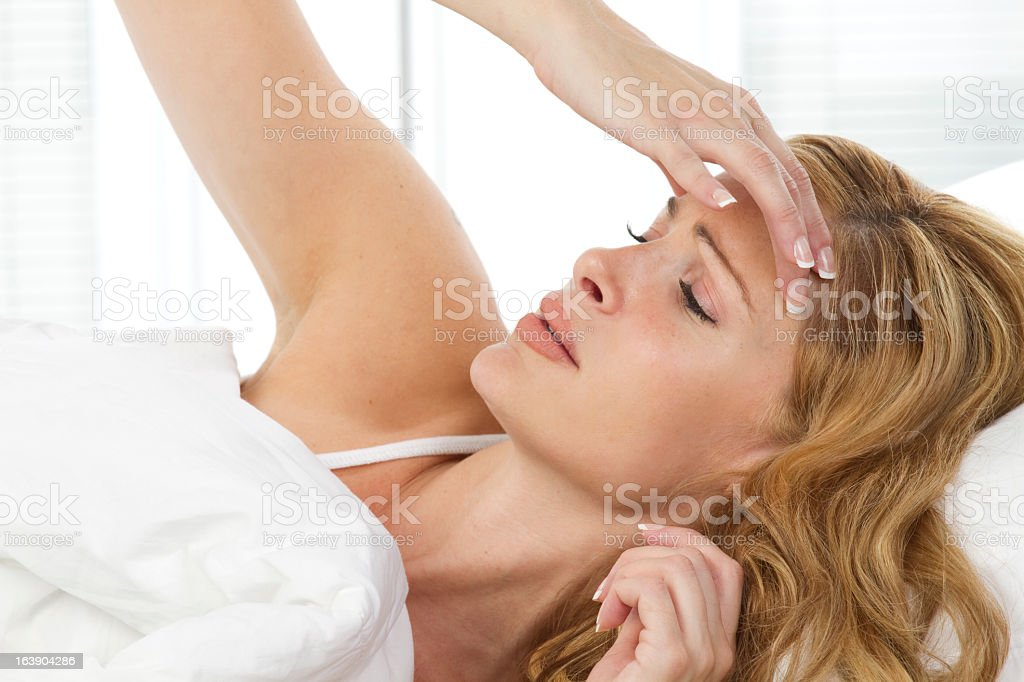 A woman touching her head in pain royalty-free stock photo
