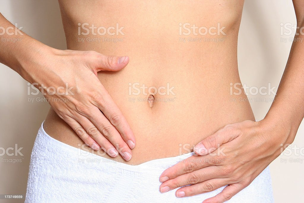 A woman touching her stomach wearing a white towel stock photo