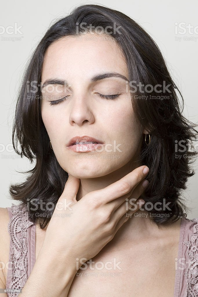 Woman touching her throat looking visibly in pain stock photo