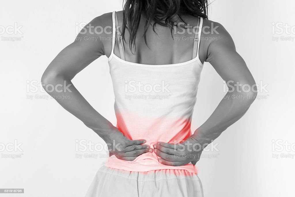 Woman touching painful back/spine. Pain in a woman back stock photo