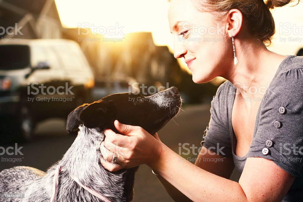 A woman touching the neck of her dog royalty-free stock photo