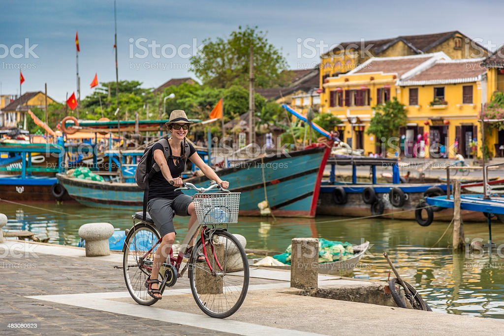 Woman Tourist Cycling in Hoi An City, Vietnam stock photo