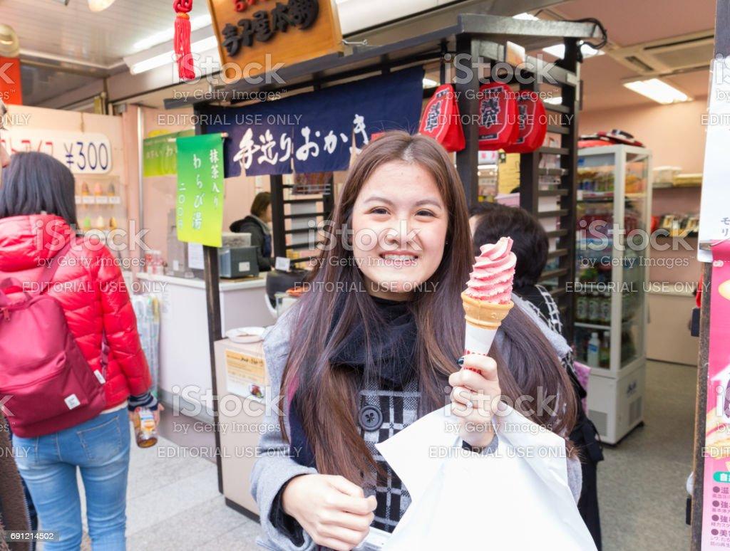 woman tourist holds the pink sakura ice cream in Nakamise the market near Sensoji temple February 18, 2017 in Tokyo, Japan stock photo