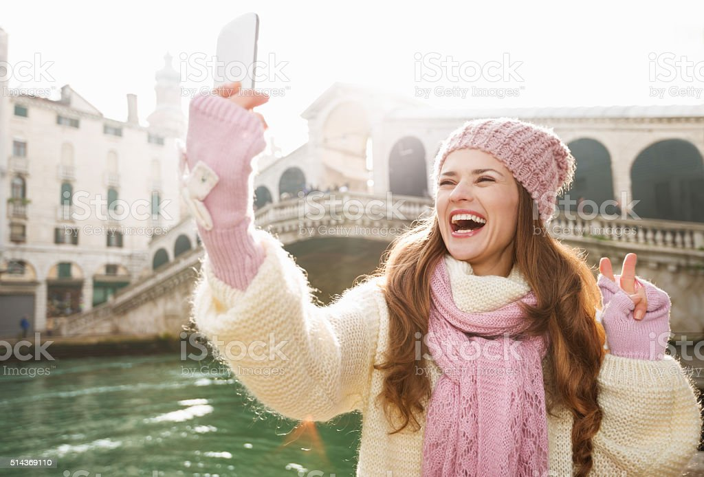 Woman tourist showing victory while taking selfie in Venice stock photo