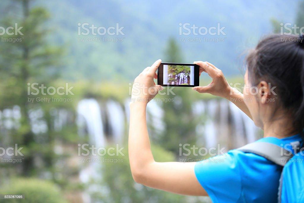 woman tourist taking photo with smart phone stock photo