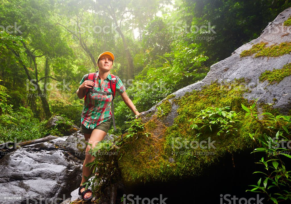 Woman tourist with backpack walking along the trail in  jungle stock photo
