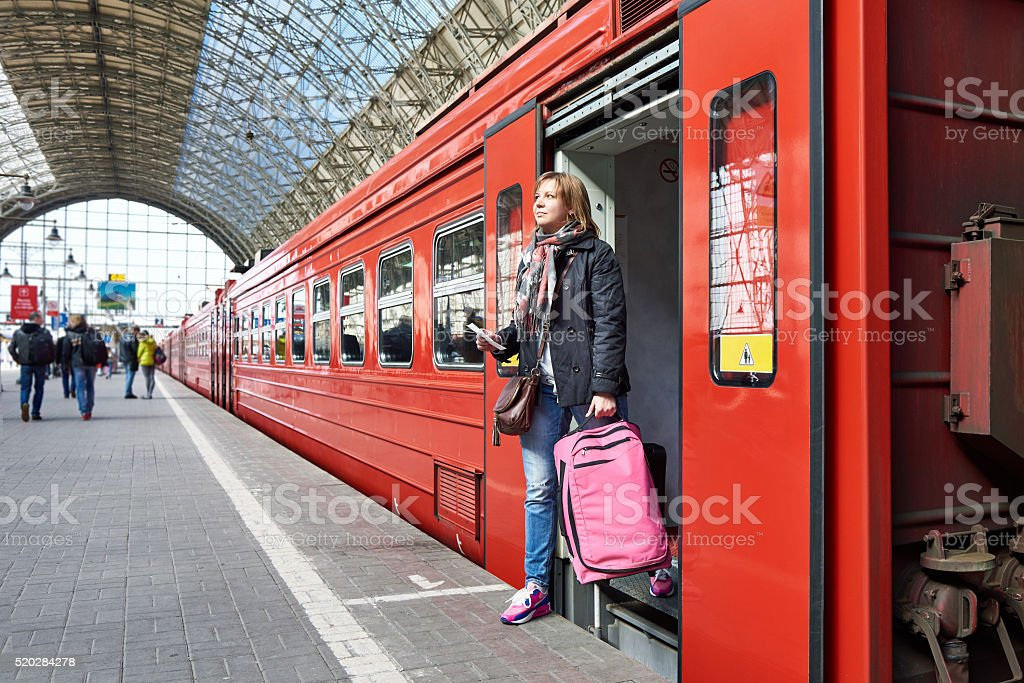 Woman tourist with suitcase coming out of train at station stock photo