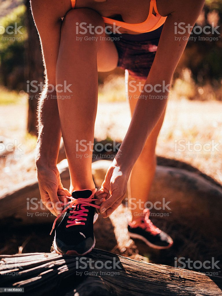 Woman trail runner fixing her shoelaces on her running shoes stock photo