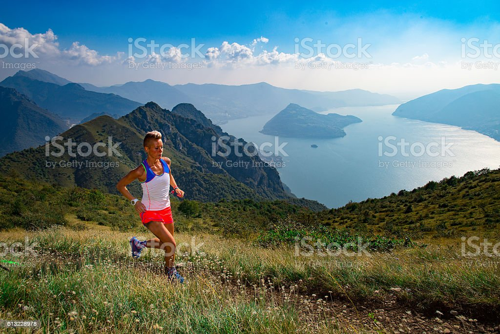 Woman trail running in the mountains athlete trains stock photo