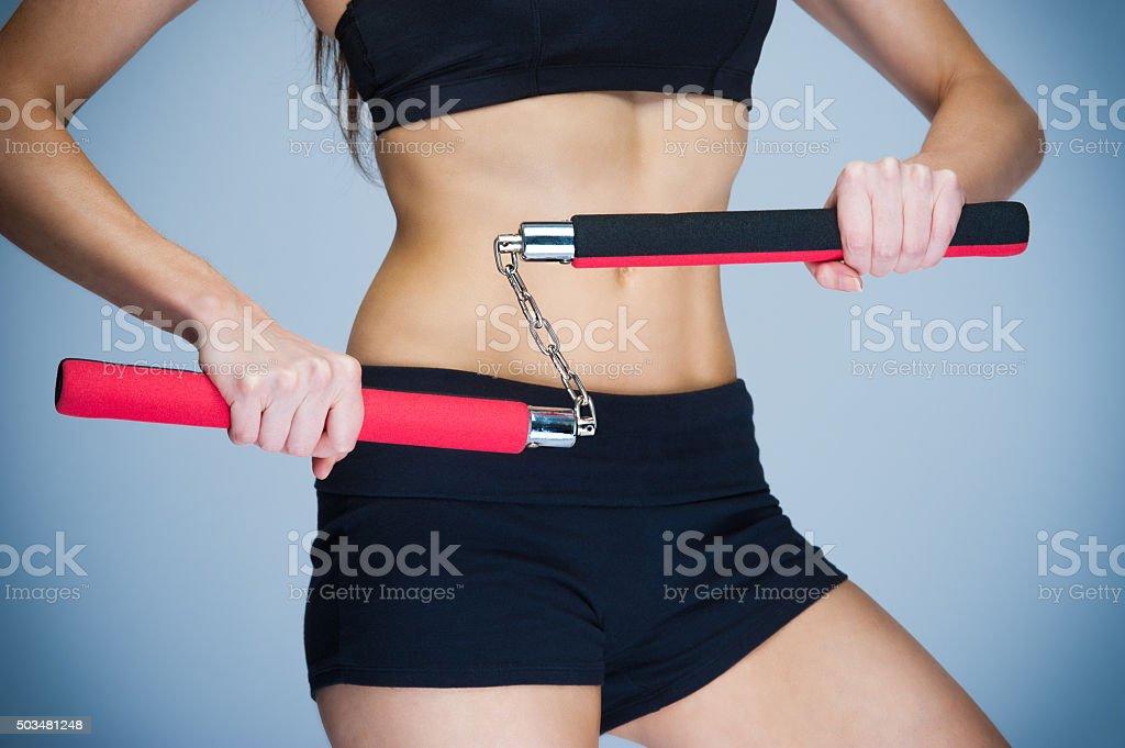 Woman Training with Nunchaku stock photo