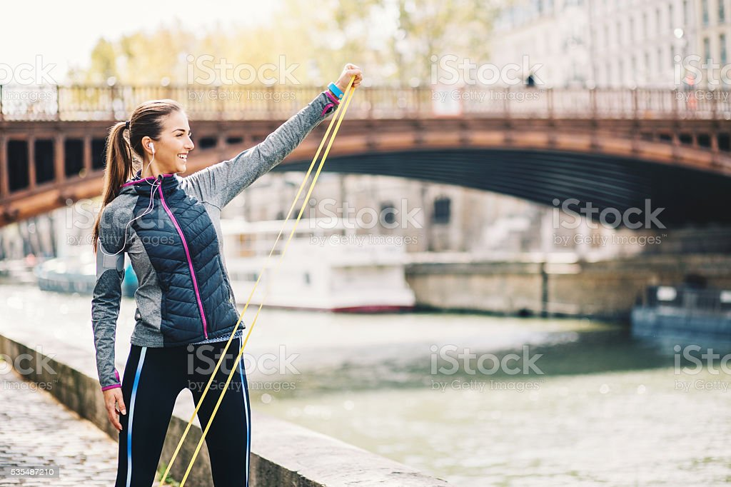 Woman training with resistance band outsoors stock photo