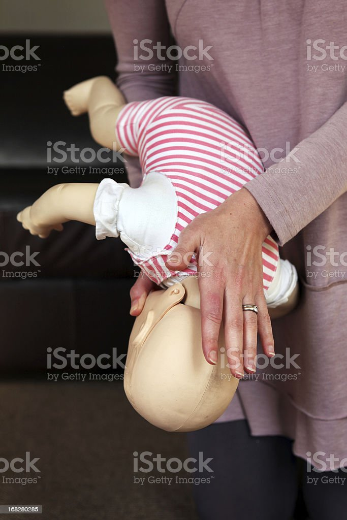 A woman trains to help a baby that is choking stock photo