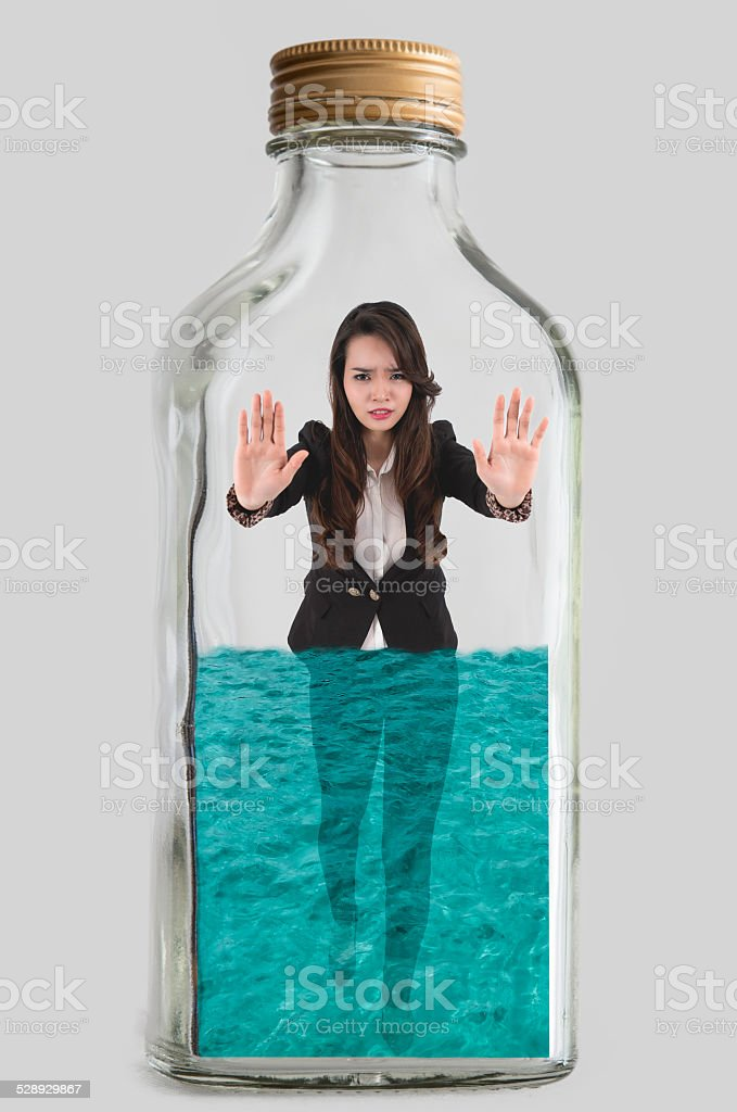 Woman trapped inside a bottle of water stock photo