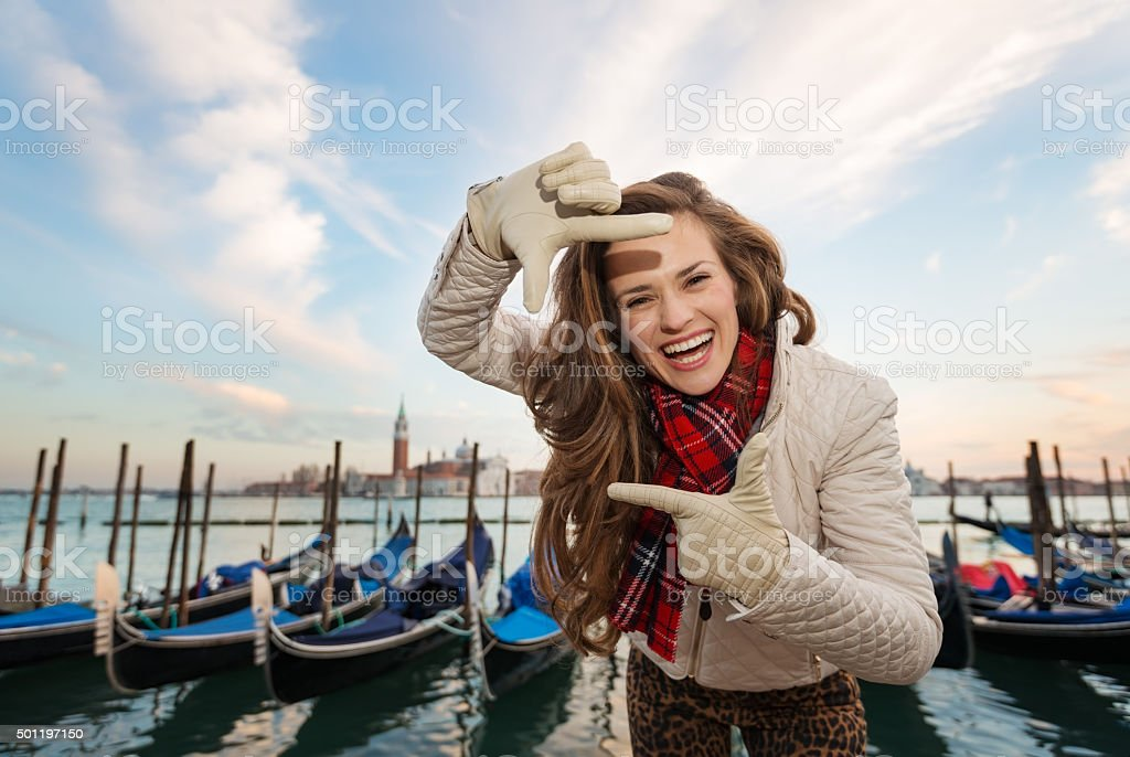 Woman traveler framing with hands on embankment in Venice, Italy stock photo