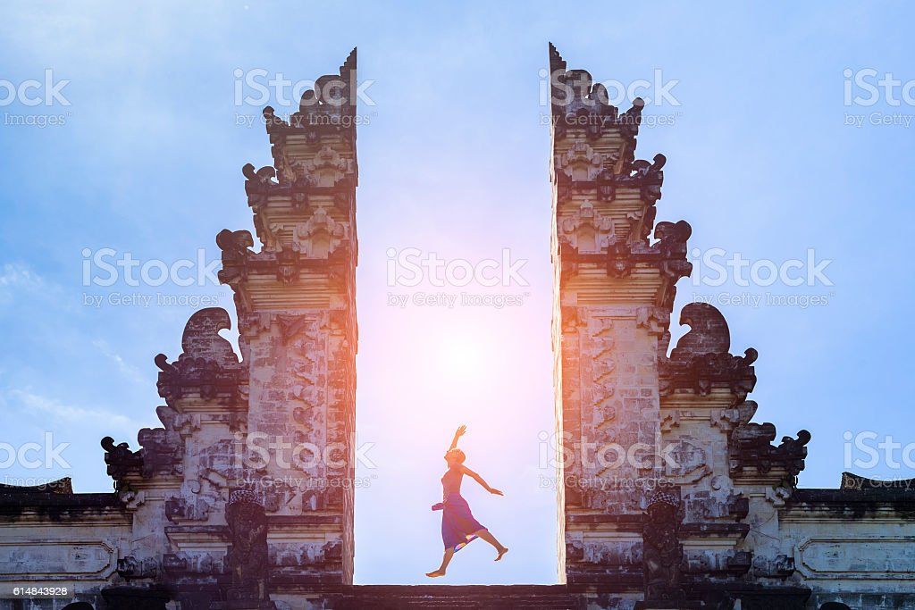 Woman traveler jumping with energy in gate temple, Bali, Indonesia stock photo