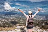 Woman traveler on high mountain, hands up