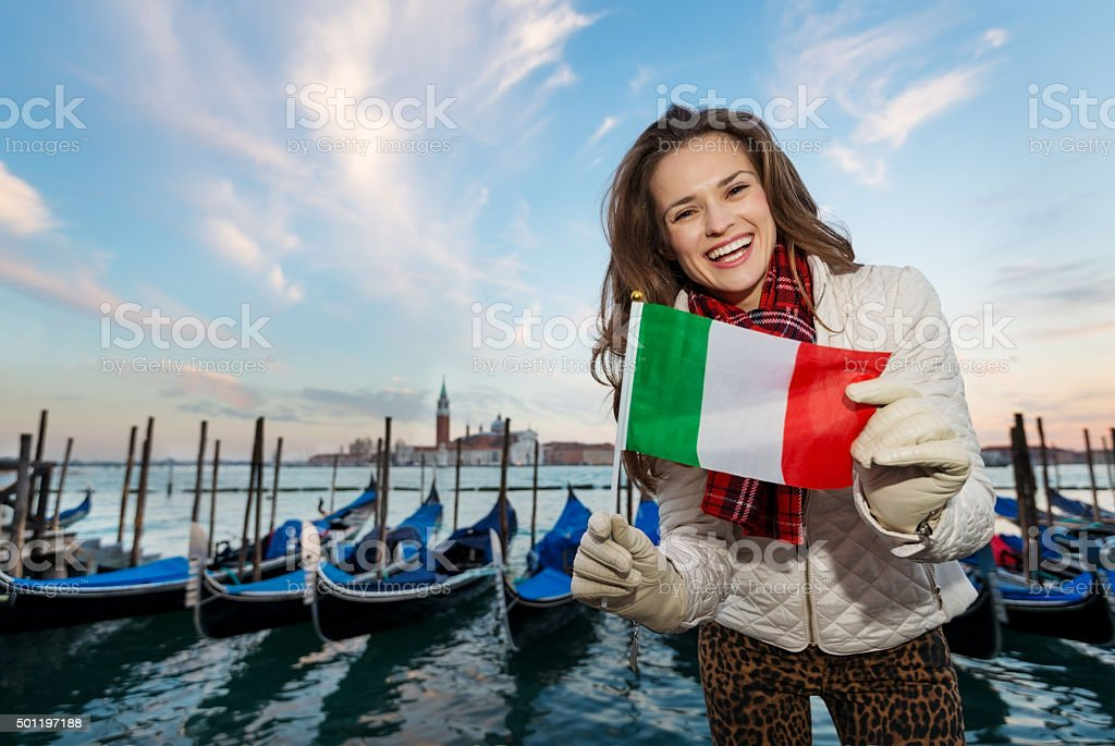 Woman traveler showing Italian flag on embankment in Venice stock photo