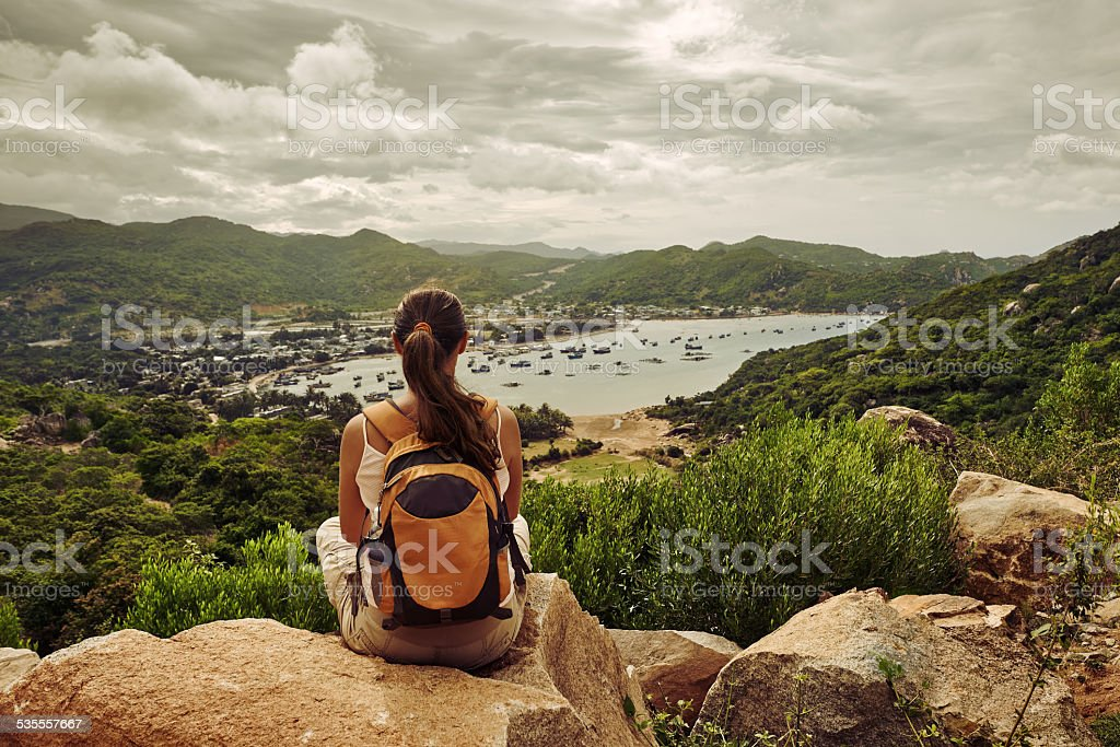 Woman traveler sits looks at edge of cliff sea bay stock photo