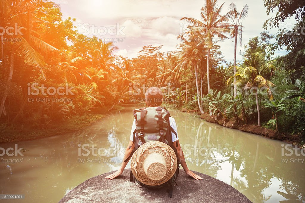 Woman traveler sitting near tropical river stock photo