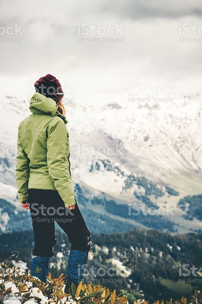 Woman Traveler standing alone Lifestyle adventure concept snow mountains stock photo