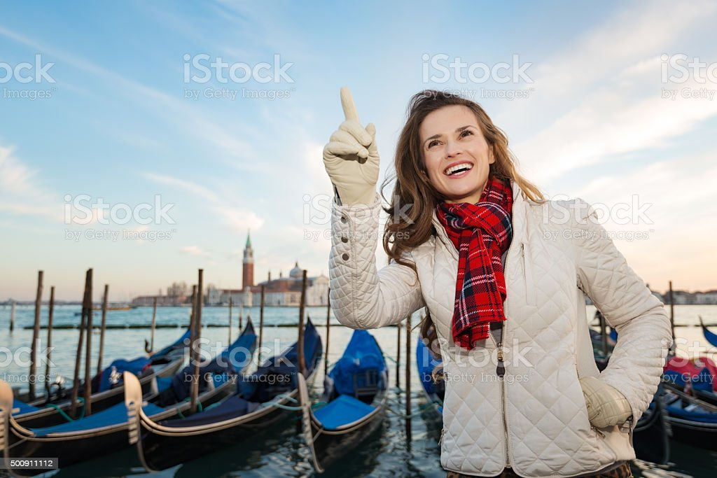 Woman traveler standing on embankment in Venice and pointing up stock photo
