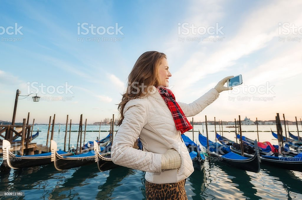 Woman traveler taking photos on embankment in Venice, Italy stock photo