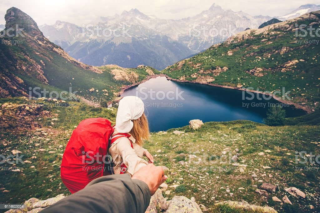 Woman Traveler with backpack holding Man hand following Travel hiking stock photo
