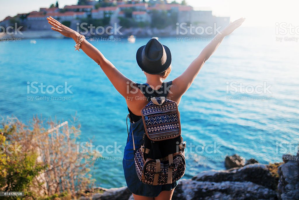Woman traveler with backpack near Sveti Stefan at Adriatic sea stock photo