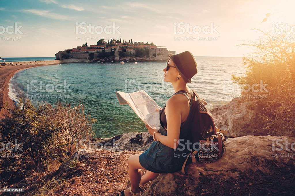 Woman traveler with map with map near sea stock photo