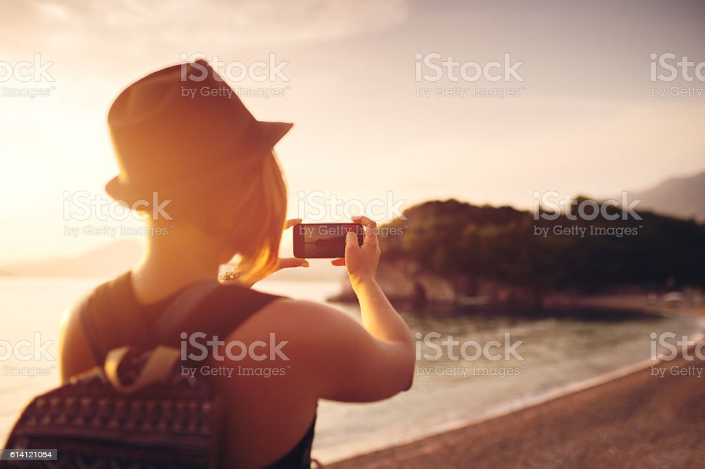 Woman traveler with smartphone taking photo near sea at sunset stock photo