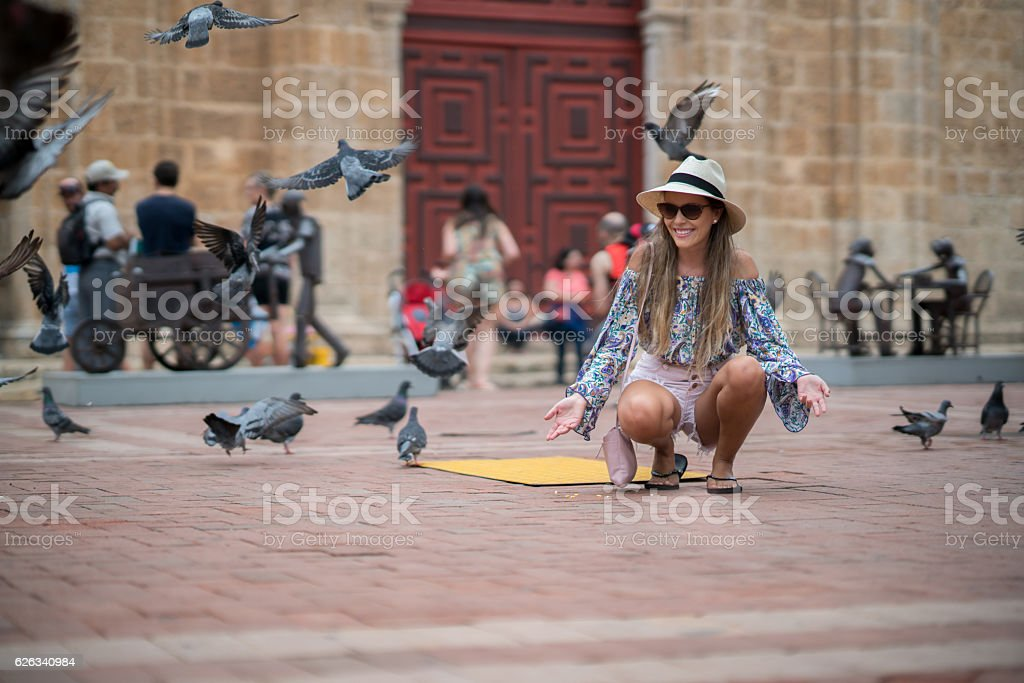 Woman traveling and feeding doves in Cartagena stock photo