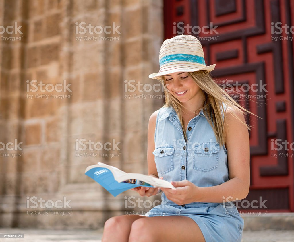 Woman traveling and holding a travel guide stock photo