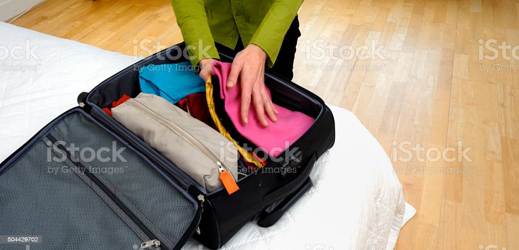 Woman traveling and packing her bag stock photo