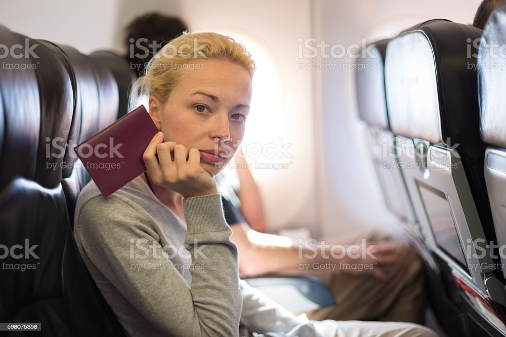 Woman traveling by plae holding passport in her hand. stock photo