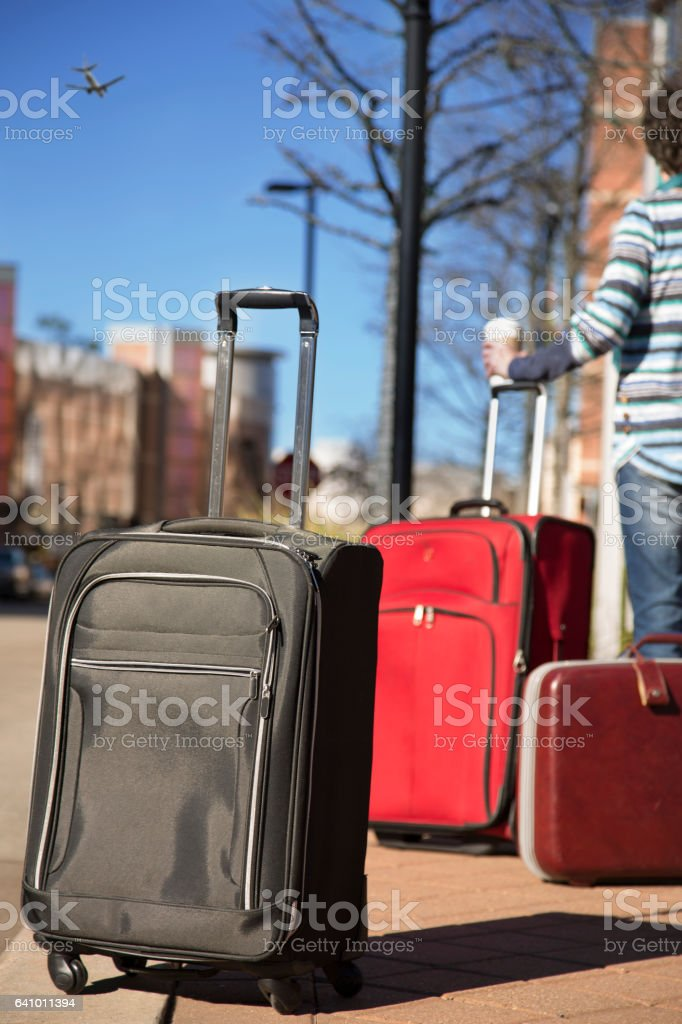 Woman traveling downtown with suitcases stock photo