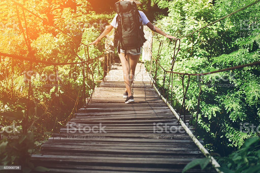 Woman traveling over hanging bridge in green forest stock photo