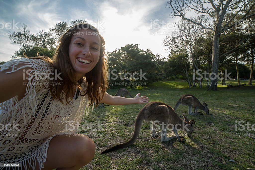 Woman traveling takes selfie portrait with kangaroos on background stock photo