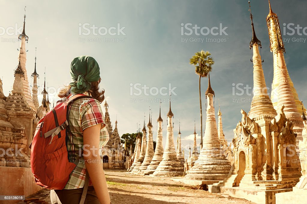 Woman traveling  with backpack and looks at Buddhist stupas stock photo